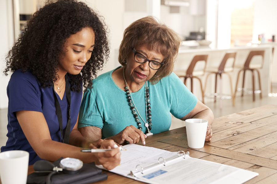 Medicare Health Plans - Healthcare Worker Helping Fill Out Forms