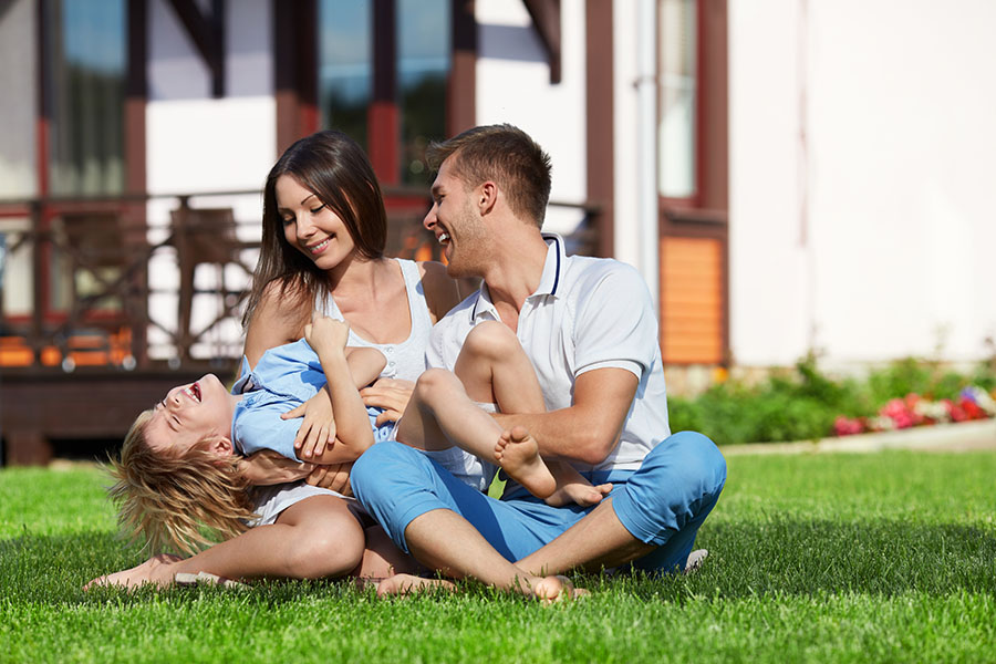 Personal Insurance - Happy Family Sitting on Grass Outside Their Home Playing Together