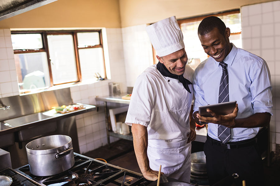 Specialized Business Insurance - Restaurant Manager and Chef Using Tablet in the Kitchen